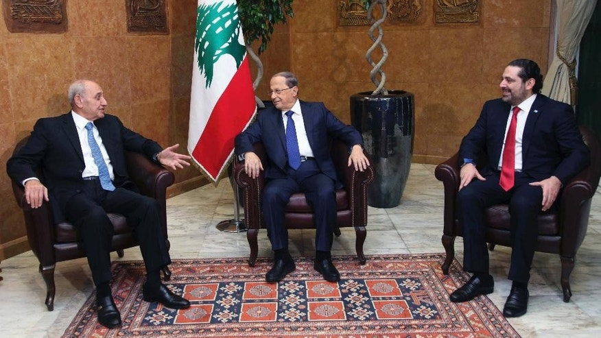 In this photo released by the Lebanese Government, Lebanese President Michel Aoun, center, meets with Lebanese Prime Minister designate, Saad Hariri, right, and Parliament Speaker Nabih Berri, left, at the Presidential Palace in Baabda, east of Beirut, Lebanon, Sunday, Dec. 18, 2016.  A new 30-member national unity Cabinet headed by prime minister Saad Hariri has been announced in Lebanon seven weeks after a news president was elected. (Dalati Nohra/Lebanese Government via AP)