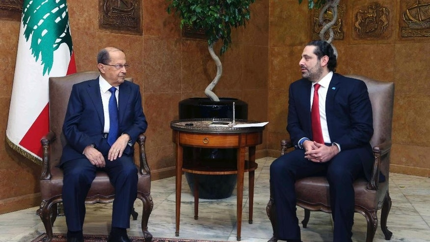 In this photo released by the Lebanese Government, Lebanese President Michel Aoun, left, meets with Lebanese Prime Minister designate, Saad Hariri, at the Presidential Palace in Baabda, east of Beirut, Lebanon, Sunday, Dec. 18, 2016. A new 30-member national unity Cabinet headed by prime minister Saad Hariri has been announced in Lebanon seven weeks after a news president was elected. (Dalati Nohra/Lebanese Government via AP)