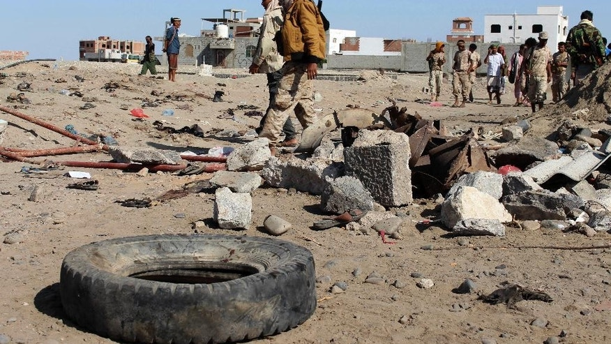 Soldiers gather the site of a suicide bomb at a base in the southern city of Aden, Yemen, Sunday, Dec. 18, 2016. A suicide bomber blew himself up outside a military camp in the southern Yemeni city of Aden on Sunday morning, killing at least 48 soldiers, a Health Ministry official said. The Health Ministry told The Associated Press that 84 people were injured in the blast. (AP Photo/Wael Qubady)