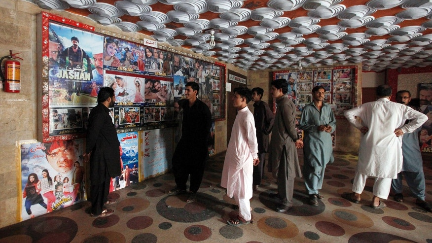 Pakistani cinema-goers look at photos displayed at a local cinema in Karachi, Pakistan, Sunday, Dec. 18, 2016.