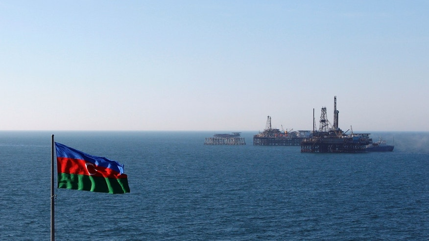 An Azerbaijan state flag flutters in the wind on an oil platform in the Caspian Sea east of Baku, January 22, 2013.
