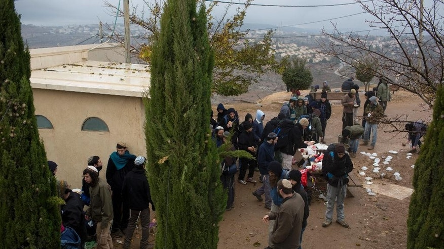Jewish settlers gather around a synagogue in Amona, an unauthorized Israeli outpost in the West Bank, east of the Palestinian town of Ramallah, Sunday, Dec. 18, 2016. Jewish settlers say they have accepted a government proposal to evacuate the outpost and move to a nearby location. Israel's Supreme Court has determined that the Amona outpost was built on private Palestinian land and has ordered the government to tear down the outpost's 50 trailer homes. (AP Photo/Oded Balilty)