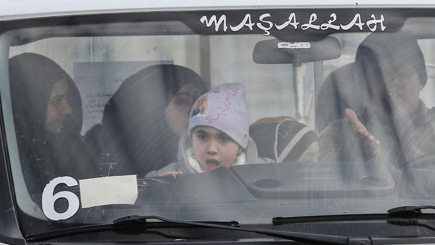 Members of a Syrian family are driven after crossing into Turkey at the Cilvegozu border gate with Syria, near Hatay, southeastern Turkey, Sunday, Dec. 18, 2016. Several people were able to cross into Turkey after they managed to leave the embattled Syrian city. The Aleppo evacuation was suspended Friday after a report of shooting at a crossing point into the enclave by both sides of the conflict. (AP Photo/Emrah Gurel)