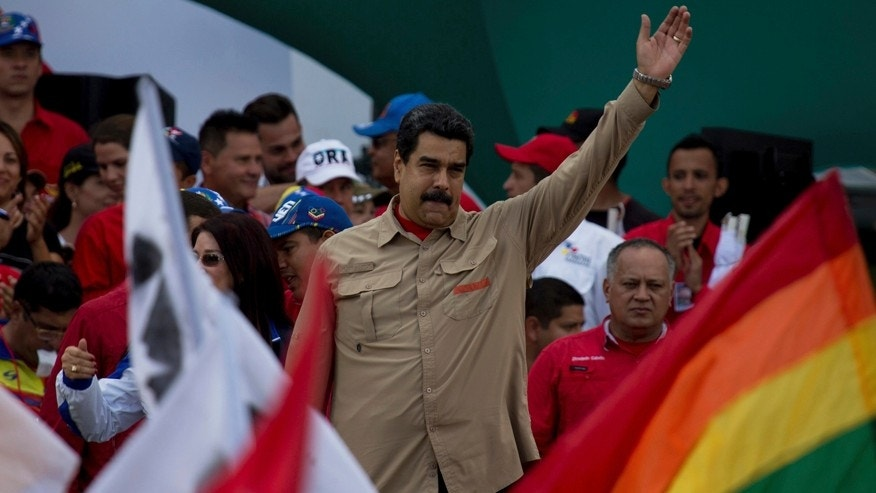 Venezuela's President Nicolas Maduro greets supporters upon his arrival to a rally at Bolivar Avenue in Caracas, Venezuela, Saturday, Dec. 17, 2016. Maduro called for a pro-government rally as the country to give a tribute to the Venezuelan hero Simon Bolivar meanwhile the country is on edge over his so-far failed plan to introduce larger-denominated bills to fight soaring inflation. (AP Photo/Fernando Llano)