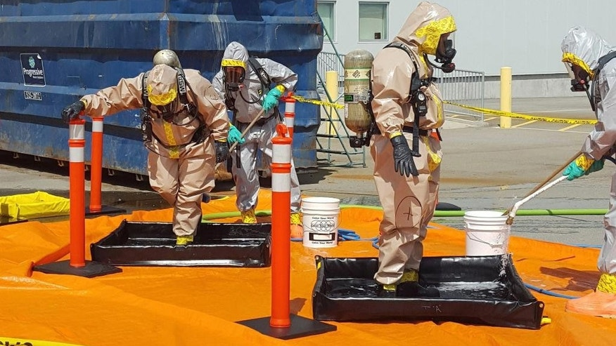 FILE - In this June 27, 2016 file photo provided by the Royal Canadian Mounted Police, members of the RCMP go through a decontamination procedure in Vancouver after intercepting a package containing approximately 1 kilogram (2.2 pounds) of the powerful opioid carfentanil imported from China. U.S. assertions that China is the top source of the synthetic opioids that have killed thousands of drug users in the U.S. and Canada are unsubstantiated, Chinese officials told the Associated Press. (Royal Canadian Mounted Police via AP, File)