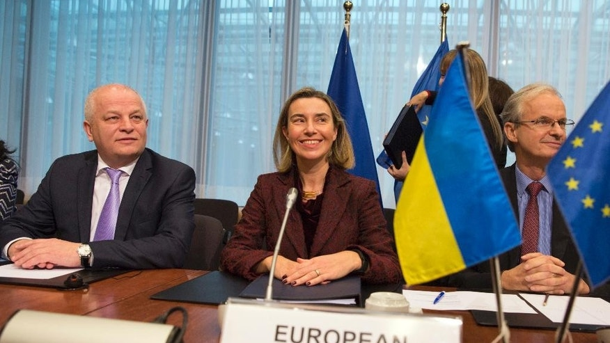 European Union High Representative Federica Mogherini, center, and Ukraine's Vice-Prime Minister Stepan Kubiv, left, wait for the start of an EU-Ukraine summit at the EU Council building in Brussels on Monday, Dec. 19, 2016. The EU and Ukraine are assessing their relations during a meeting between EU foreign affairs chief Federica Mogherini and Ukraine government representatives. (AP Photo/Virginia Mayo)