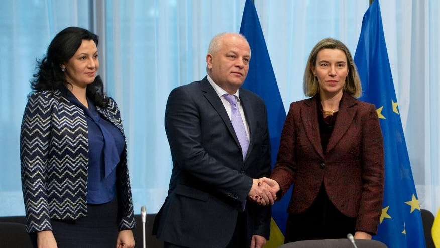 European Union High Representative Federica Mogherini, right, shakes hands with Ukraine's Vice-Prime Minister Stepan Kubiv, center, during an EU-Ukraine summit at the EU Council building in Brussels on Monday, Dec. 19, 2016. The EU and Ukraine are assessing their relations during a meeting between EU foreign affairs chief Federica Mogherini and Ukraine government representatives. At left is Ukrainian Deputy Vice Prime Minister Ivanna Klympush-Tsyntsadze. (AP Photo/Virginia Mayo)