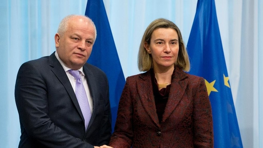 European Union High Representative Federica Mogherini, right, shakes hands with Ukraine's Vice-Prime Minister Stepan Kubiv during an EU-Ukraine summit at the EU Council building in Brussels on Monday, Dec. 19, 2016. The EU and Ukraine are assessing their relations during a meeting between EU foreign affairs chief Federica Mogherini and Ukraine government representatives. (AP Photo/Virginia Mayo)