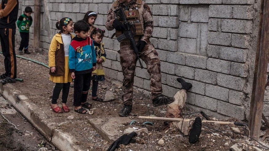 In this Sunday, Dec. 18, 2016 photo, Iraqi children look at the body of a half-buried Islamic State militant while talking to an Iraqi soldier in the al-Barid district in Mosul, Iraq. In a part of Mosul that had been reclaimed from the Islamic State group (IS) days ago, Iraqi special forces were attacked on Sunday by drones operated by IS fighters inside the city.(AP Photo/Manu Brabo)