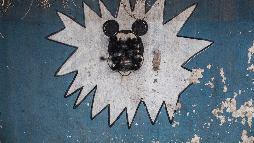 This Sunday, Dec. 18, 2016 photo shows a drawing of Mickey Mouse with its face painted over by Islamic States militants on the wall of a kindergarten n the al-Barid district in Mosul, Iraq. In a part of Mosul that had been reclaimed from the Islamic State group (IS) days ago, Iraqi special forces were attacked on Sunday by drones operated by IS fighters inside the city.(AP Photo/Manu Brabo)
