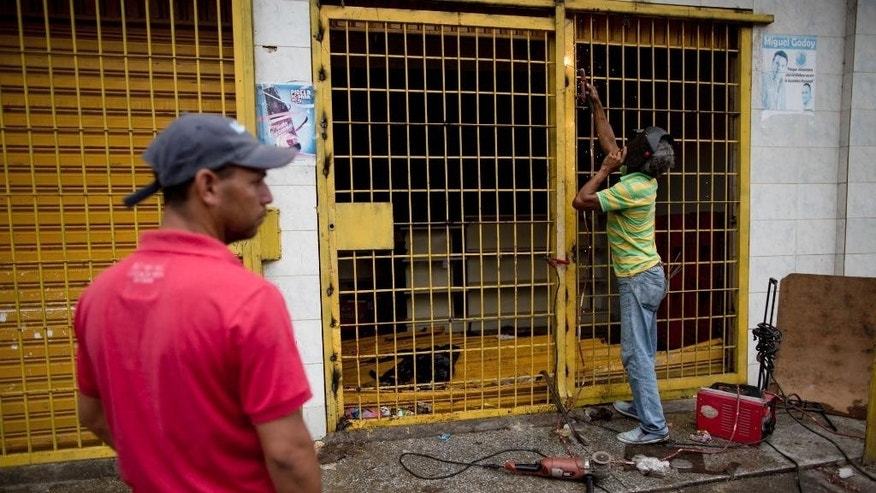 A store owner repairs the security gate at the entrance to his grocery store looted by demonstrators the night before, in Ciudad Bolivar, Venezuela, Monday, Dec. 19, 2016. Last week, President Nicolas Maduro made an announcement annulling all 100-bolivar notes leading to massive lines at banks, and cash transactions such as buying food or gasoline extremely difficult. Maduro suddenly changed course late Saturday, announcing the 100-bolivar notes could be used until Jan. 2. Before that announcement riots and looting broke out in several cities. (AP Photo/Alejandro Cegarra)