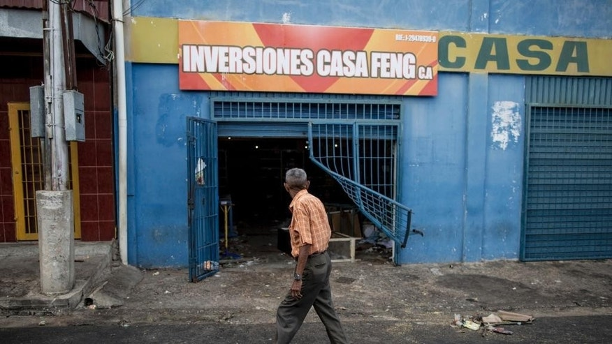 A man walks past a grocery store looted by demonstrators the night before in Ciudad Bolivar, Venezuela, Monday, Dec. 19, 2016. Last week, President Nicolas Maduro made an announcement annulling all 100-bolivar notes leading to massive lines at banks, and cash transactions such as buying food or gasoline extremely difficult. Maduro suddenly changed course late Saturday, announcing the 100-bolivar notes could be used until Jan. 2. Before that announcement riots and looting broke out in several cities. (AP Photo/Alejandro Cegarra)