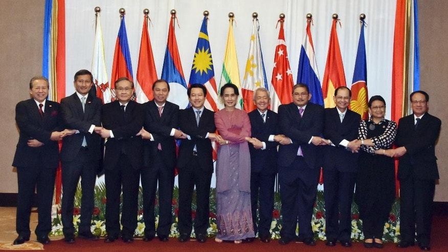 In this photo released by Myanmar State Media, Myanmar Foreign Minister Aung San Suu Kyi, center, links with foreign ministers from Association of Southeast Asian Nations (ASEAN) before their meeting at a hotel Monday, Dec.19, 2016, in Yangon, Myanmar. (Myanmar State Media via AP)