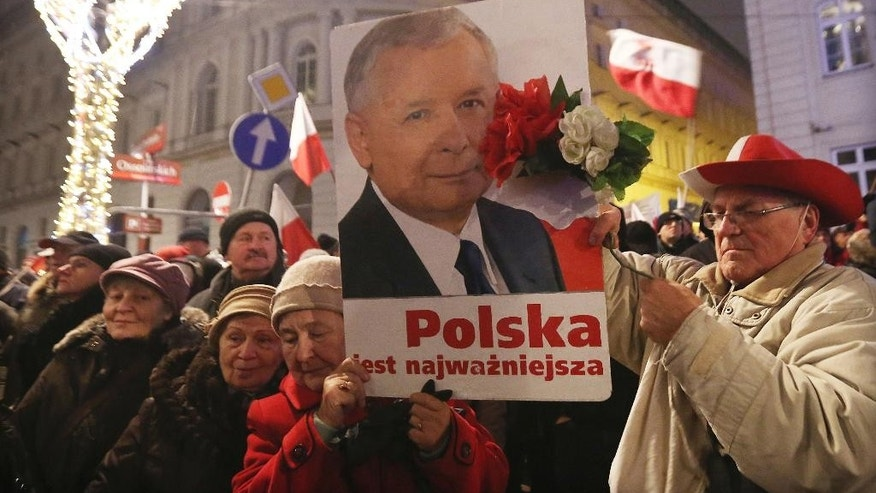 Supporters of the ruling Law and Justice party with a portrait of the leader Jaroslaw Kaczynski as they attend a pro-government rally in front of the presidential palace, in Warsaw, Poland, Sunday, Dec. 18, 2016. Political tension is rising between Poland's conservative government and the pro-EU opposition.(AP Photo/Czarek Sokolowski)