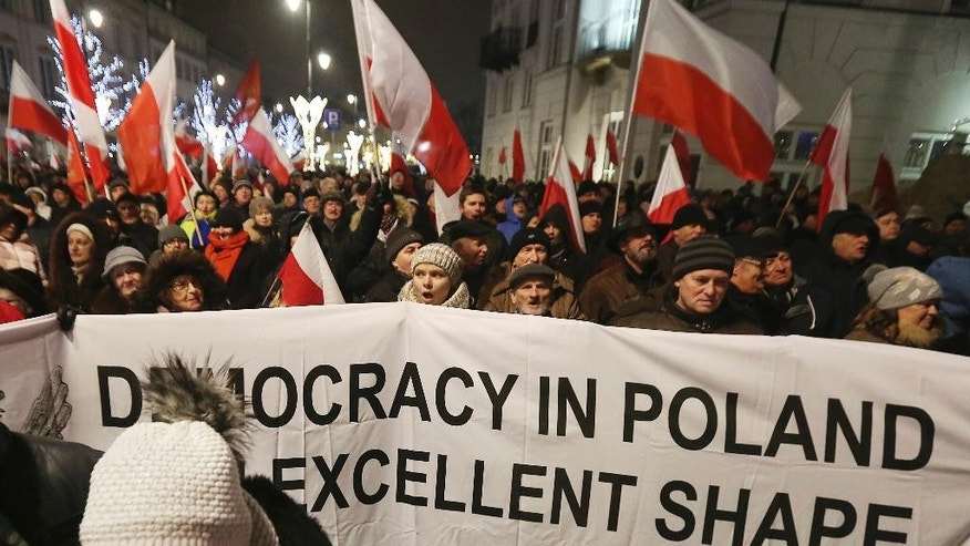 Supporters of the ruling Law and Justice party shout slogans as they attend a pro-government rally in front of the presidential palace, in Warsaw, Poland, Sunday, Dec. 18, 2016. Political tension is rising between Poland's conservative government and the pro-EU opposition.(AP Photo/Czarek Sokolowski)