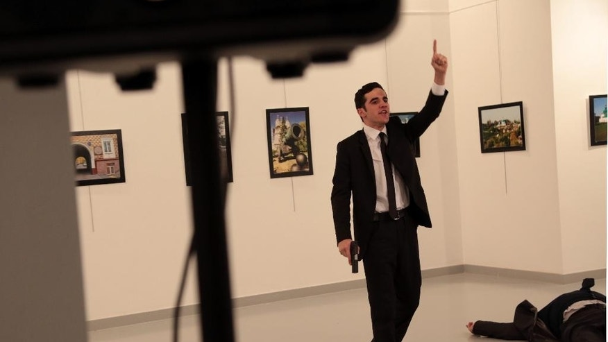 A man gestures near to Andrei Karlov on ground,  the Russian Ambassador to Turkey at a photo gallery in Ankara, Turkey, Monday, Dec. 19, 2016. An Associated Press photographer says a gunman has fired shots at the Russian ambassador to Turkey. The ambassador's condition wasn't immediately known. (AP Photo/Burhan Ozbilici)