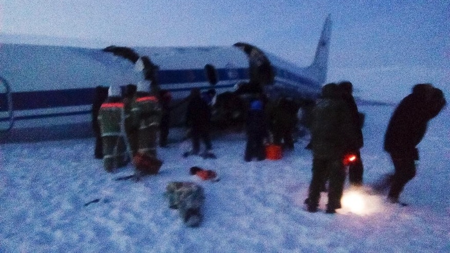In this handout photo released by Yakutsk.ru web portal shows Emergency Ministry employees investigate the wreckage of an Il-18 turboprop, that crash-landed about 30 kilometers (19 miles) from the town of Tiksi in the Sakha-Yakutia region on the Laptev Sea, Russia, Monday, Dec. 19, 2016. A Russian military plane crash-landed Monday while approaching an Arctic airport, injuring most of the 39 people on board, officials said. (Yakutsk.ru photo via AP)