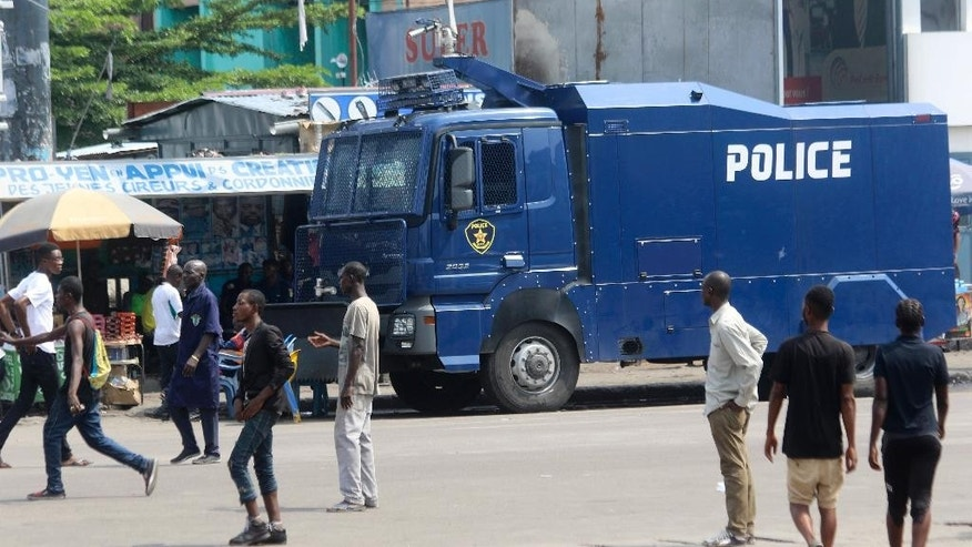People walk past a police truck  in Kinshasa, Congo, Monday, Dec. 19, 2016. Military and police units are deployed across the capital of Congo amid fears of unrest on the last official day of President Joseph Kabila's mandate. Kabila intends to stay on after the midnight deadline, as a court has ruled he can stay in power until new elections are held.   (AP Photo/John Bompengo)