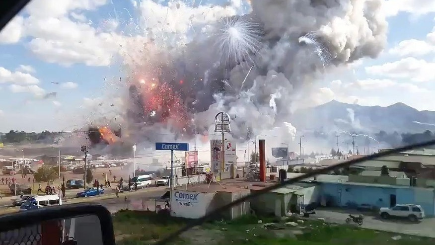 This image made from video recorded from a passing car shows an explosion ripping through the San Pablito fireworks' market in Tultepec, Mexico, Tuesday, Dec. 20, 2016. Sirens wailed and a heavy scent of gunpowder lingered in the air after the afternoon blast at the market, where most of the fireworks stalls were completely leveled. According to the Mexico state prosecutor there are at least 26 dead. (Jose Luis Tolentino via AP)