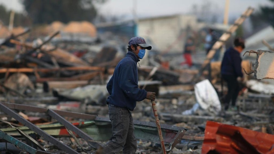 A man walks  through the scorched ground of the open-air San Pablito fireworks market, in Tultepec, outskirts of Mexico City, Mexico, Tuesday, Dec. 20, 2016.  An explosion ripped through Mexico's best-known fireworks market where most of the fireworks stalls were completely leveled. According to the Mexico state prosecutor there are dozens dead. (AP Photo/Eduardo Verdugo)