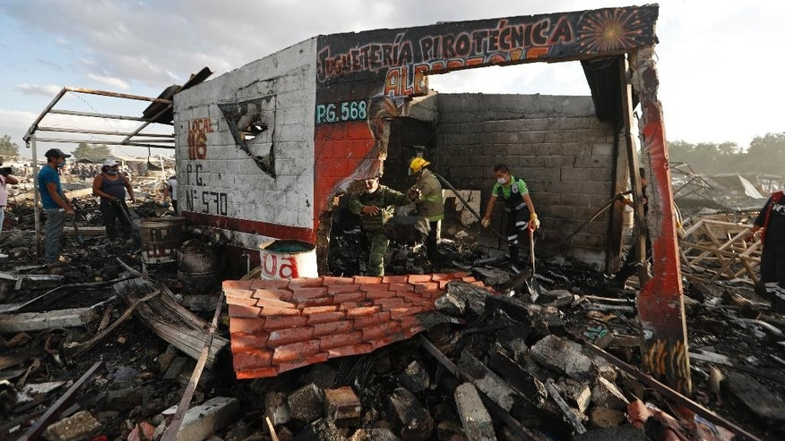 Firefighters and rescue workers remove debris from the scorched ground of Mexico's best-known fireworks market after an explosion explosion ripped through it, in Tultepec, on the outskirts of Mexico City, Mexico, Tuesday, Dec. 20, 2016. National Civil Protection Coordinator Luis Felipe Puente told Milenio TV that dozens were hurt but he had no immediate report of any fatalities at the open-air San Pablito Market in Tultepec, in the State of Mexico. (AP Photo/Eduardo Verdugo)