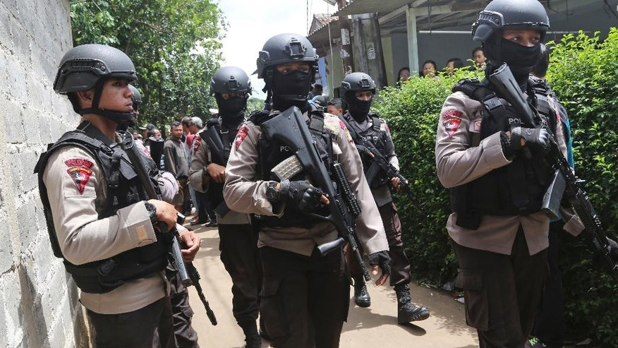 Police officers stand guard at a residential neighborhood where police conducted a raid on a house used by suspected militants, in Tangerang, Indonesia Wednesday, Dec. 21, 2016. Indonesian police said three suspected militants who were planning a holiday season suicide bombing were killed in the raid Wednesday on the outskirts of Jakarta in the second imminent attack to be foiled in less than two weeks. (AP Photo/Tatan Syuflana)