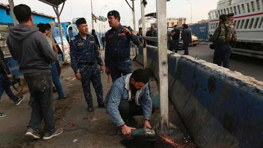 Iraqi security forces dismantle a checkpoint in Baghdad, Iraq, Tuesday, Dec. 20, 2016. Iraqi authorities say they have started removing some of the security checkpoints in Baghdad in a bid to ease traffic in the country's capital. The development appears to reflect the government's confidence in its ability to secure Baghdad _ even as it wages a weeks-long offensive to take back Mosul, Iraq's second-largest city, from the Islamic State group. (AP Photo/Hadi Mizban)