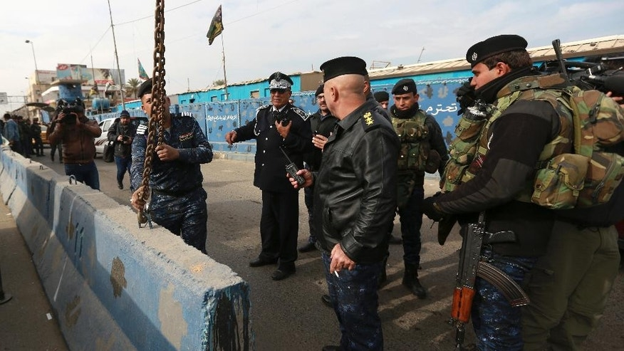 Iraqi security forces remove a concrete barrier in Baghdad, Iraq, Tuesday, Dec. 20, 2016. Iraqi authorities say they have started removing some of the security checkpoints in Baghdad in a bid to ease traffic in the country's capital. The development appears to reflect the government's confidence in its ability to secure Baghdad _ even as it wages a weeks-long offensive to take back Mosul, Iraq's second-largest city, from the Islamic State group.  (AP Photo/Hadi Mizban)