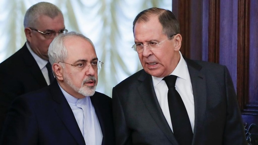 "Russian Foreign Minister Sergey Lavrov, right, and Iranian Foreign Minister Mohammad Javad Zarif talk to each other as they enter a hall for the talks in Moscow, Russia, Tuesday, Dec. 20, 2016. Foreign ministers of Russia, Turkey and Iran are meeting on Tuesday to discuss Syria, but the talks are likely to be overshadowed by the assassination of Russia's ambassador to Turkey the previous night by an Ankara policeman, who after killing his victim cried out: ""Don't forget Aleppo! Don't forget Syria!"" (AP Photo/Pavel Golovkin)"