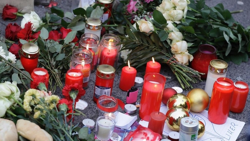 Candles burn near the crime scene in Berlin, Germany, Tuesday, Dec. 20, 2016, the day after a truck ran into a crowded Christmas market and killed several people. (AP Photo/Matthias Schrader)