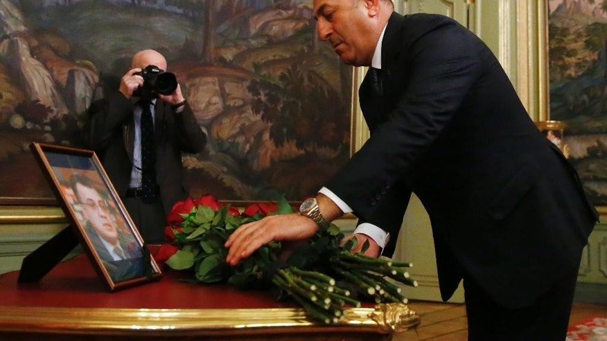 Turkey's Foreign Minister Mevlut Cavusoglu offers flowers in memory of Russian Ambassador to Turkey Andrei Karlov, who was fatally shot by a Turkish policeman Monday in a gathering in Ankara, Turkey, before their talks on Syria in Moscow, Russia, Tuesday, Dec. 20, 2016. (Maxim Shemetov/Pool Photo via AP)