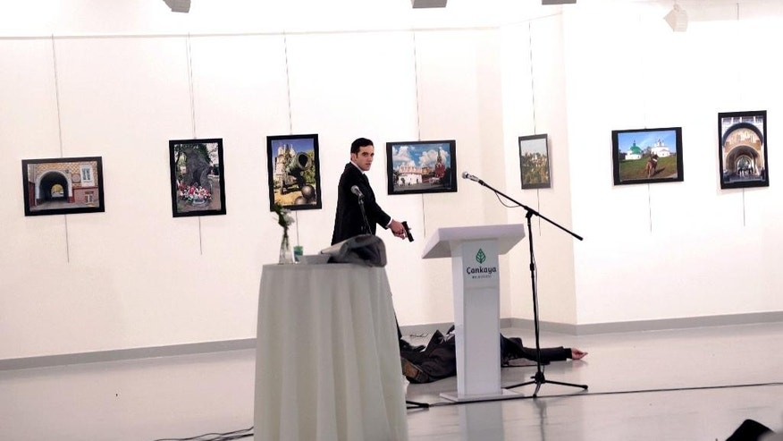 ADDS THE NAME OF THE GUNMAN - A man identified as Mevlut Mert Altintas stands over Andrei Karlov, the Russian Ambassador to Turkey, after shooting him at a photo gallery in Ankara, Turkey, Monday, Dec. 19, 2016. Karlov, 62, was several minutes into a speech at the embassy-sponsored exhibition when Altintas fatally shot him in front of stunned onlookers. (AP Photo/Burhan Ozbilici)