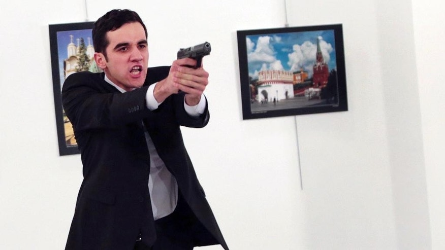 "ADDS THE NAME OF THE GUNMAN - A man identified as Mevlut Mert Altintas holds up a gun after shooting Andrei Karlov, the Russian Ambassador to Turkey, at a photo gallery in Ankara, Turkey, Monday, Dec. 19, 2016. Shouting ""Don't forget Aleppo! Don't forget Syria!"" Altintas fatally shot Karlov in front of stunned onlookers at a photo exhibit. Police killed the assailant after a shootout. (AP Photo/Burhan Ozbilici)"