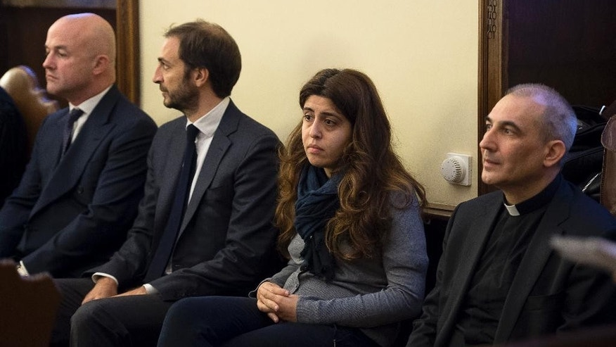 "FILE - In this Nov. 24, 2015 file photo, from left, Italian journalists Gianluigi Nuzzi and Emiliano Fittipaldi, public relations expert Francesca Chaouqui and Monsignor Angelo Lucio Vallejo Balda sit during their trial inside the Vatican. Pope Francis has freed a Vatican monsignor convicted of leaking confidential documents to journalists, granting him a Christmas-time clemency and ending an embrarrassing episode for the Holy See. The Vatican said late Tuesday, Dec. 20, 2016 that Francis had granted ""conditional freedom"" to Spanish Monsignor Lucio Vallejo Balda. Fired from his job as a high-ranking Vatican financial official, Vallejo now falls under the authority of his local bishop in Astorga, Spain. (L'Osservatore Romano/Pool Photo via AP)"