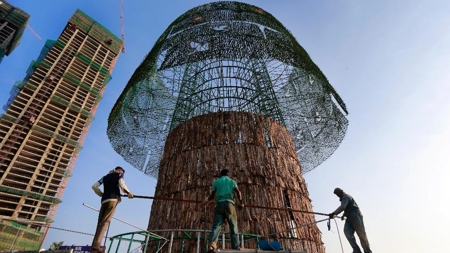 In this Thursday, Dec. 15, 2016 photo, Sri Lankan port workers carry steel rods as they try to build an enormous, artificial Christmas tree on a popular beachside promenade in Colombo, Sri Lanka. Hundreds of Sri Lanka's port workers and volunteers are struggling to put up the towering Christmas tree in time for the holidays. The majority-Buddhist nation is aiming to beat the world record for the tallest, artificial Christmas tree as a show of multicultural respect. But twice the construction deadline was missed, and now organizers hope to erect the tree on Christmas Eve. The Catholic Church has criticized the $80,000 price tag as a waste of money that is better spent helping the poor. (AP Photo/Eranga Jayawardena)