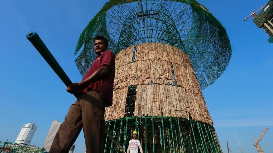 In this Thursday, Dec. 15, 2016 photo, Haloluwage Don Nanayakkara, left, carries a steel rod with another worker as they try to build an enormous, artificial Christmas tree on a popular beachside promenade in Colombo, Sri Lanka. The idea for the tree came from this Buddhist driver at Colombo's port who makes decorations in his spare time. Hundreds of Sri Lanka's port workers and volunteers are struggling to put up the towering Christmas tree in time for the holidays. The majority-Buddhist nation is aiming to beat the world record for the tallest, artificial Christmas tree as a show of multicultural respect. But twice the construction deadline was missed, and now organizers hope to erect the tree on Christmas Eve. The Catholic Church has criticized the $80,000 price tag as a waste of money that is better spent helping the poor. (AP Photo/Eranga Jayawardena)