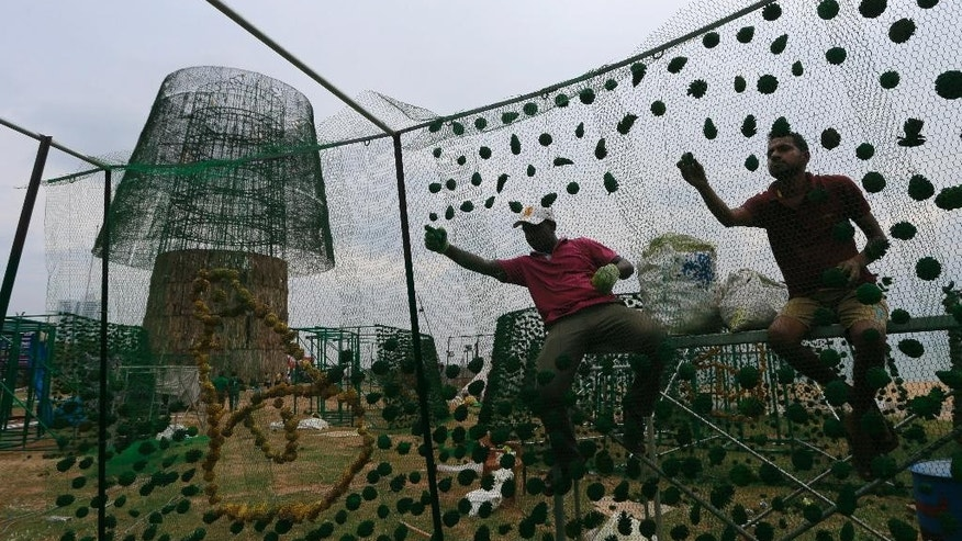 In this Monday, Dec. 19, 2016 photo, Sri Lankan port workers assemble decorations on frames as they try to build an enormous, artificial Christmas tree on a popular beachside promenade in Colombo, Sri Lanka. Hundreds of Sri Lanka's port workers and volunteers are struggling to put up the towering Christmas tree in time for the holidays. The majority-Buddhist nation is aiming to beat the world record for the tallest, artificial Christmas tree as a show of multicultural respect. But twice the construction deadline was missed, and now organizers hope to erect the tree on Christmas Eve. The Catholic Church has criticized the $80,000 price tag as a waste of money that is better spent helping the poor. (AP Photo/Eranga Jayawardena)