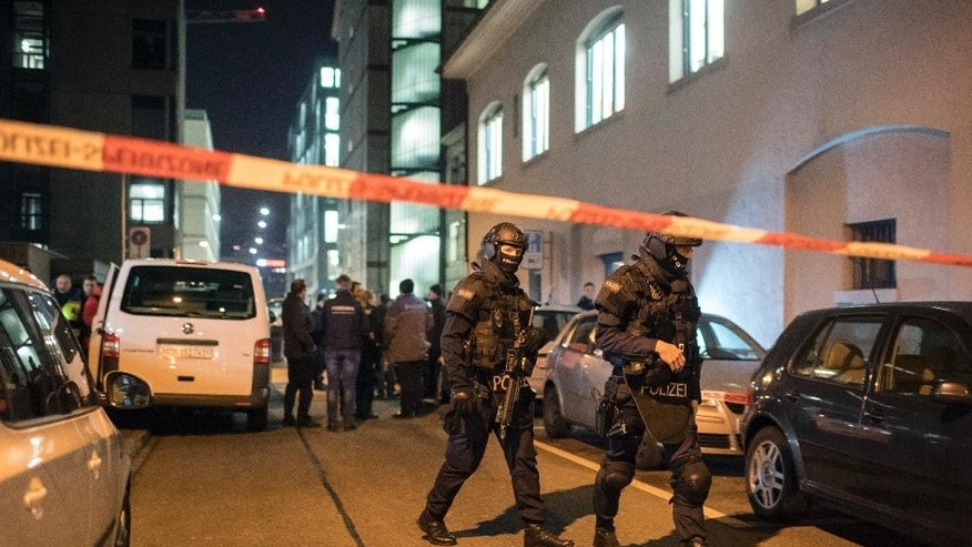 Special Unit Policemen secure the area in front of the Islamic center, in Zurich, Monday, Dec. 19, 2016. A Zurich police official says a gunman has injured several people in Switzerland's largest city. The official said police were swarming to the scene in pursuit of the gunman who remains at large. (Ennio Leanza/Keystone via AP)