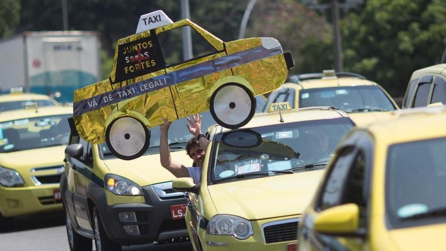 FILE - In this Nov. 11, 2015 file photo, a man holds up a mock cab as taxi drivers protest the Uber ride service in Rio de Janeiro, Brazil. Uber sees tremendous potential in Brazil, Latin America's most populous nation. The rocketing growth, however, is also a race against time: local governments are moving toward regulating and taxing the company in ways that may hurt its competitive advantage while taxi unions are pushing to ban it entirely. (AP Photo/Leo Correa, File)
