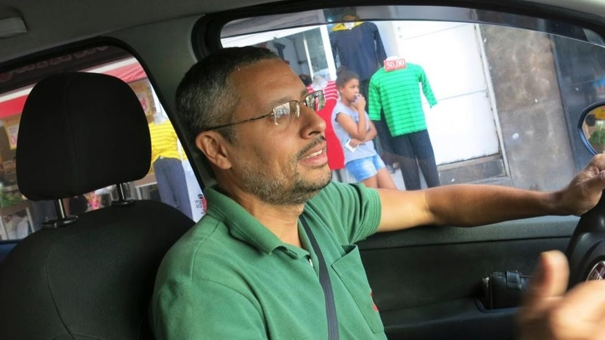 "In this Nov. 11, 2016 photo, Fabio Freitas, 37, drives his taxi in Rio de Janeiro, Brazil. Freitas said he used to make $84 per day, but now is lucky to make half of that because of competition from Uber. ""It's hard to even have hope,"" said Freitas. (AP Photo/Peter Prengaman)"