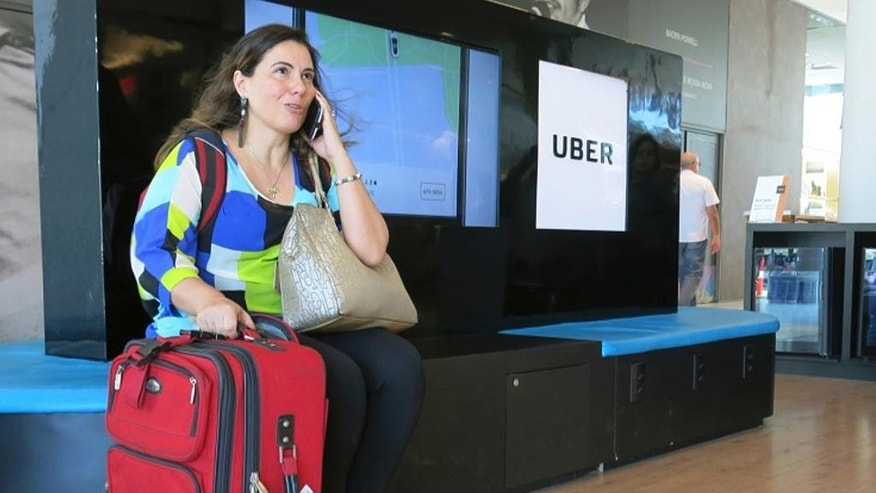 In this Nov. 11, 2016 photo, Mirella Sanches, a 41-year-old architect, waits to be picked up at an Uber stand in Rio de Janeiro,Brazil. Introduced in Brazil just over two years ago, use of the app has increased so quickly here that the country now represents Uber's third largest business worldwide, after the United States and India. (AP Photo/Peter Prengaman)