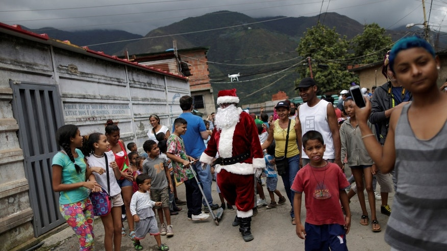 Santa Claus walks during a visit to residents of the slum of Petare in Caracas, Venezuela, December 11, 2016.