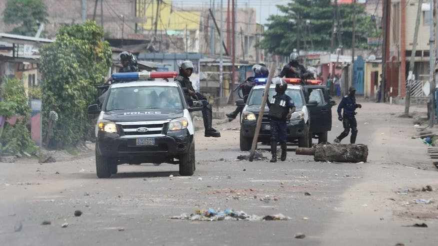 Riot police remove barricade used to block a road during a protests in Kinshasa, Democratic Republic of Congo, Tuesday, Dec. 20, 2016. Human Rights Watch says security forces have killed three people in Congo's capital and arrested scores more amid protests against President Joseph Kabila's hold on power. (AP Photo/John Bompengo)