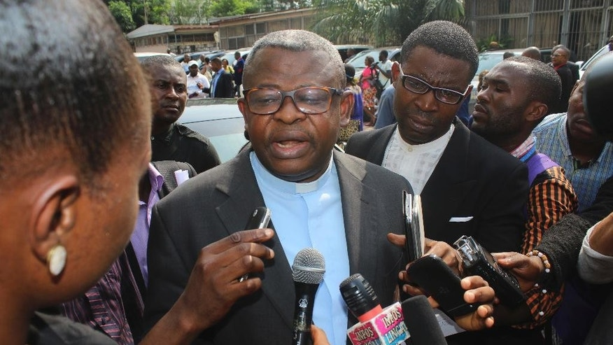 Priest Donatien Nshole, First Deputy Secretary-General of the National Episcopal Commission, speaks to journalists after a meeting in Kinshasa, Democratic Republic of Congo, Wednesday, Dec. 21, 2016. Mediators urged Congo's president and opposition parties Wednesday to reach an agreement before Christmas on a peaceful settlement to the country's political crisis, saying dozens already have been killed this week amid protests over the president's stay in power. (AP Photo/John Bompengo)