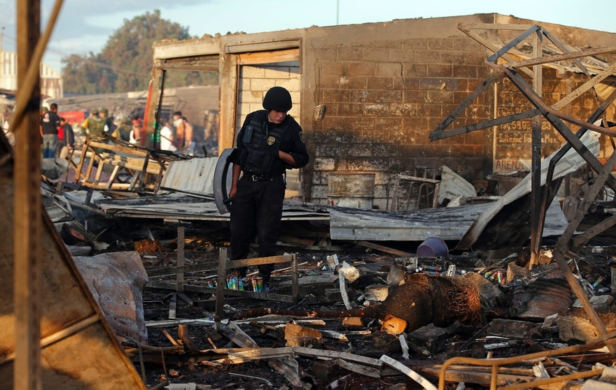 A Mexico State policeman looks through the scorched ground of the open-air San Pablito fireworks market, in Tultepec, outskirts of Mexico City, Mexico, Tuesday, Dec. 20, 2016.  An explosion ripped through Mexico's best-known fireworks market on the northern outskirts of the capital Tuesday, injuring scores and killing dozens, according to Mexican Federal Police. (AP Photo/Eduardo Verdugo)