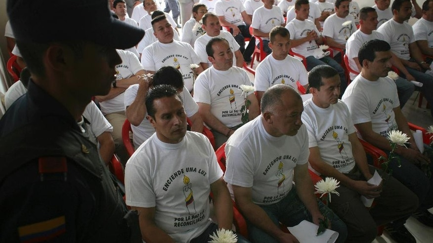"FILE - In this March 11, 2009 file photo, a group of rebels of the Revolutionary Armed Forces of Colombia attend a ceremony where they graduated as ""peacemakers"" after they renounced the rebel group and the armed struggle, at La Picota prison in southern Bogota, Colombia. Behind bars some 4,000 FARC members are waiting anxiously for January 2017, for the passage of an amnesty law that will allow them to leave behind long prison sentence and rejoin their comrades as part of a peace deal. (AP Photo/William Fernando Martinez, File)"