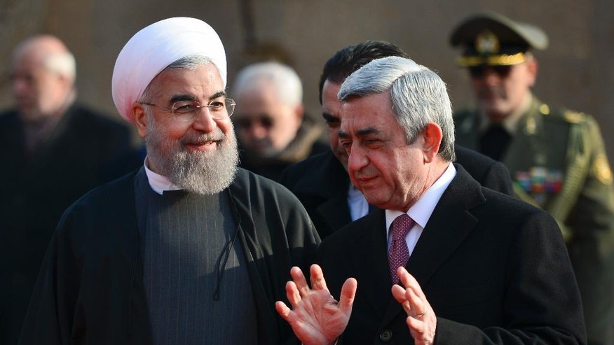 Armenian President Serzh Sargsyan, right, gestures while speaking to Iranian President Hassan Rouhani, during an official welcome ceremony at the Presidential Palace in Yerevan, Armenia, Wednesday, Dec. 21, 2016. Rouhani began his 3-day tour to Armenia, Kazakhstan and Kyrgyzstan on bilateral ties and regional developments. (Davit Hakobyan, PAN Photo via AP)