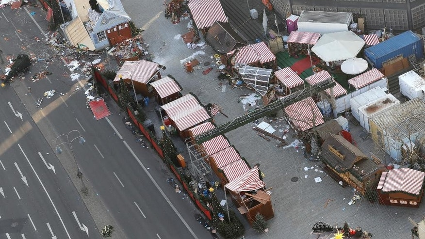 Debris still lies on the crime scene in Berlin, Germany, Wednesday, Dec. 21, 2016, two days after a truck ran into a crowded Christmas market and killed several people. (AP Photo/Michael Sohn)