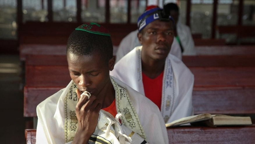 In this photo taken Thursday, Nov. 3, 2016, young Ugandan jews make prayers at the new Stern Synagogue in Mbale, eastern Uganda.  The synagogue, built largely with money donated by Americans, is a source of pride for hundreds of Ugandan Jews known locally as the Abayudaya, who have tenaciously maintained their belief despite the prejudice they have suffered over the years in this Christian-dominated country. (AP Photo/Stephen Wandera)