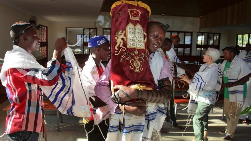In this photo taken Thursday, Nov. 3, 2016, Ugandan Jew Israel Siriri, center, carries the Torah during prayers at the new Stern Synagogue in Mbale, eastern Uganda. The synagogue, built largely with money donated by Americans, is a source of pride for hundreds of Ugandan Jews known locally as the Abayudaya, who have tenaciously maintained their belief despite the prejudice they have suffered over the years in this Christian-dominated country. (AP Photo/Stephen Wandera)